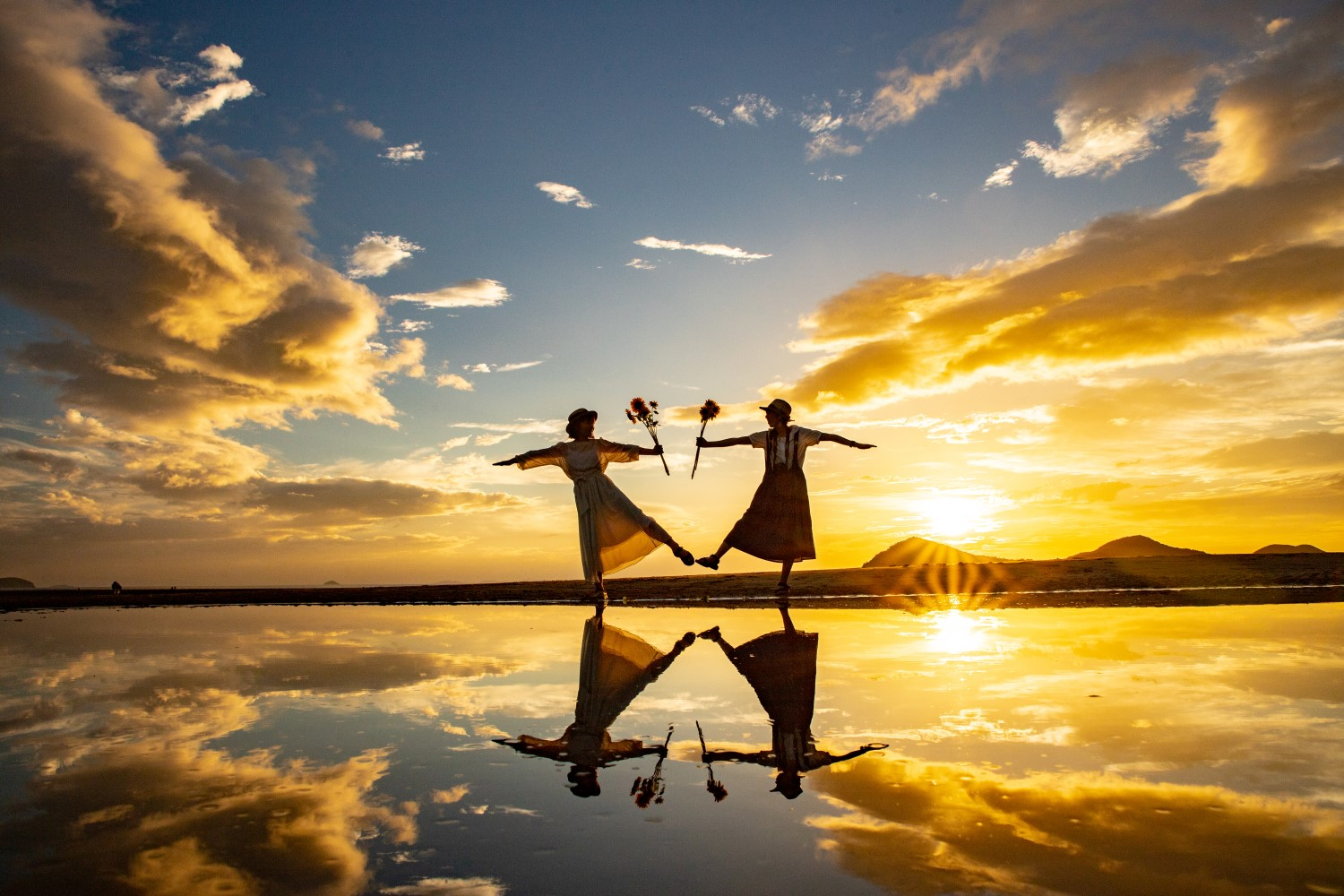 Two women standing on the beach reflected in the water below with the setting sun behind them. They are holding sunflowers and standing on one leg with the other extended, mirroring each other's pose.