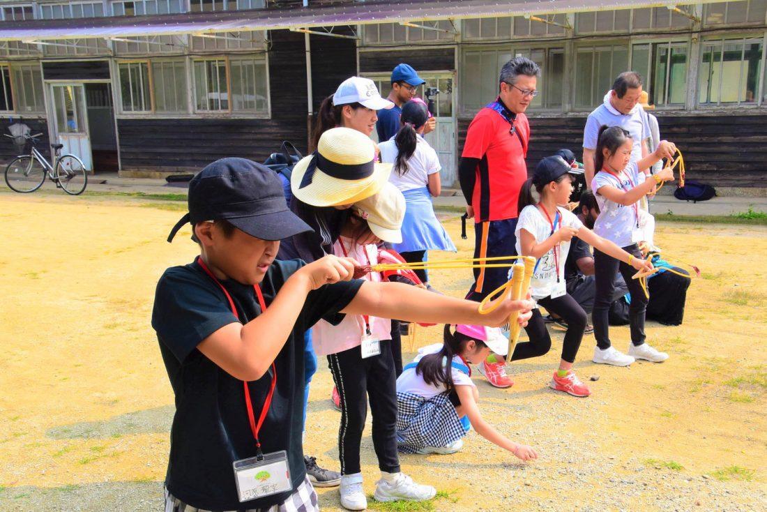 children firing slingshots